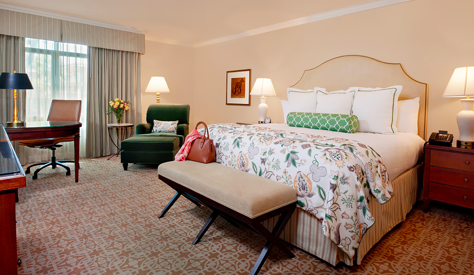 spacious suite with queen bed, footer and green lounge chair