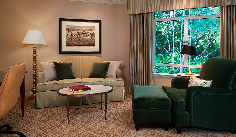 suite seating area with emerald green lounge chair and sofa with center table