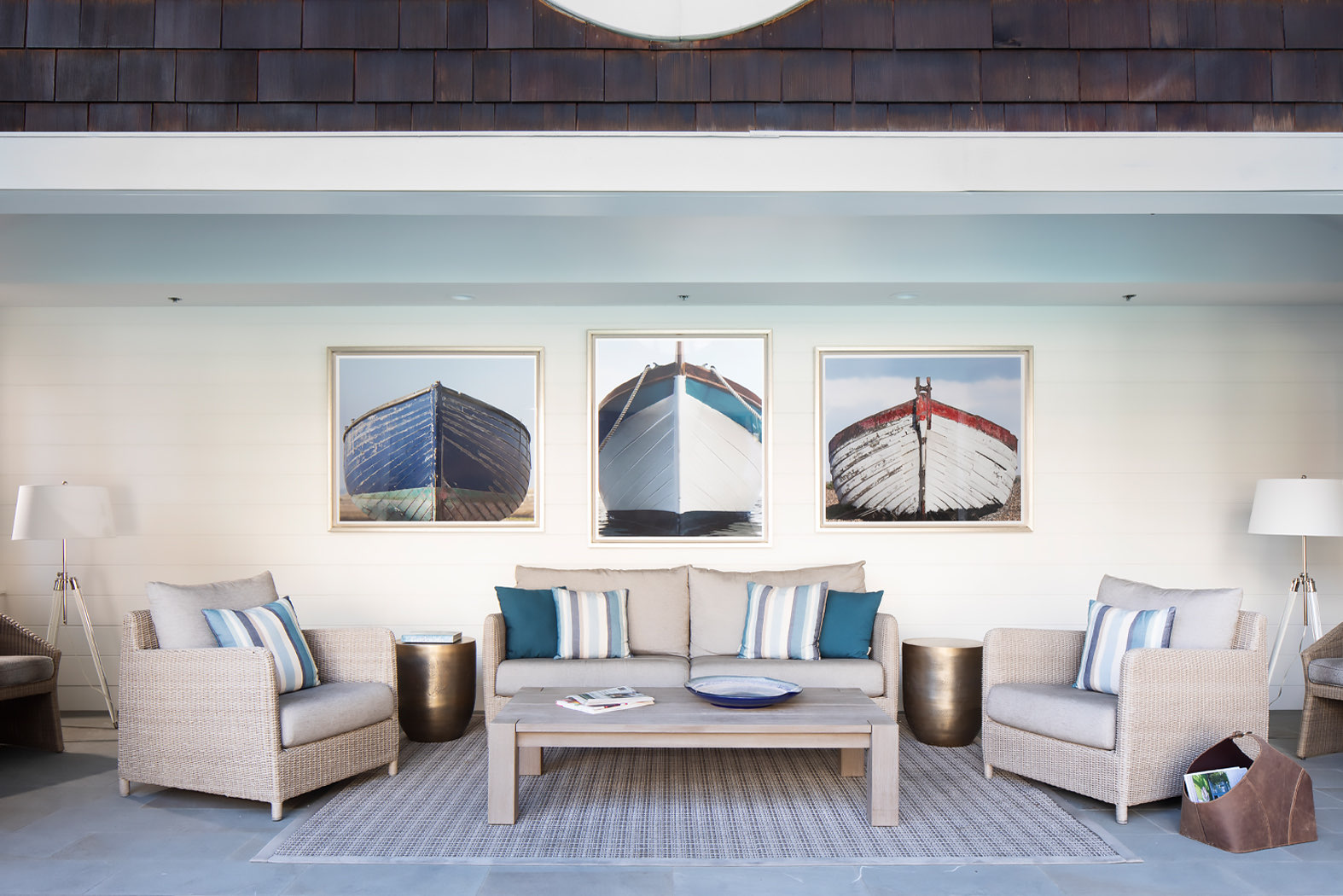 beige living room with three paintings of boats on the wall