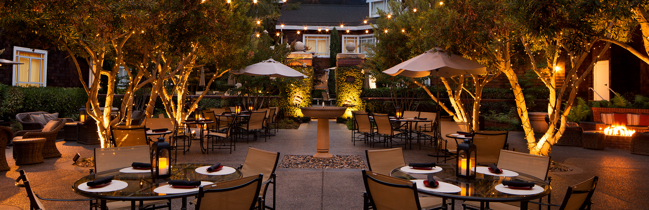 Courtyard dining tables in the evening with lighting on trees