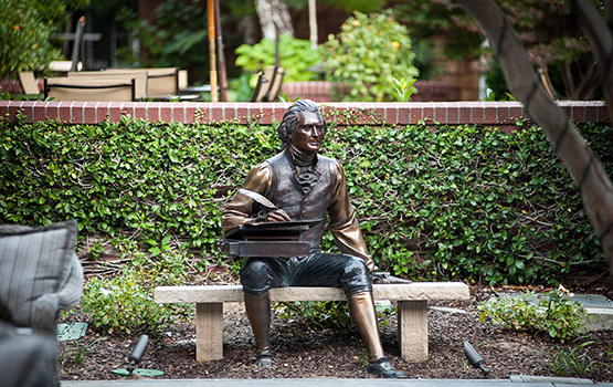 Bronze statue of writer sitting on a bench