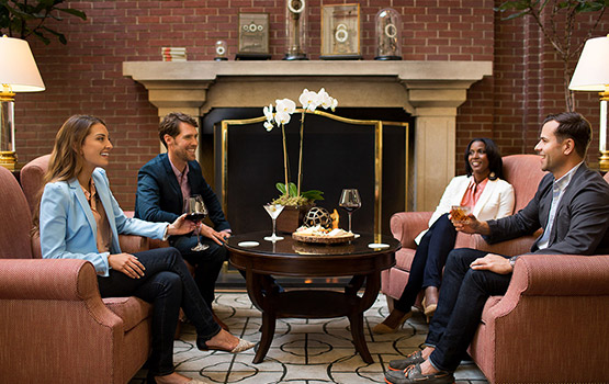 4 people sitting around a coffee table in front of a fireplace