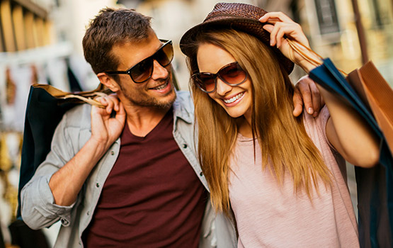 Man and woman wearing sunglasses holding black shopping bags