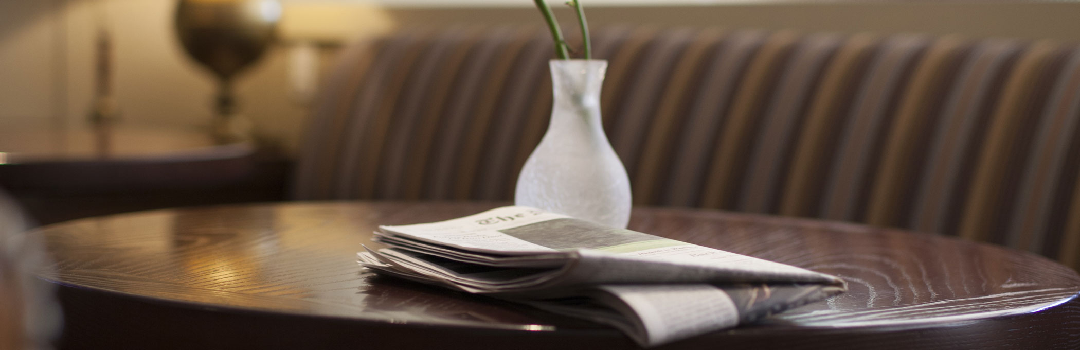 a white vase and a newspaper on a brown table