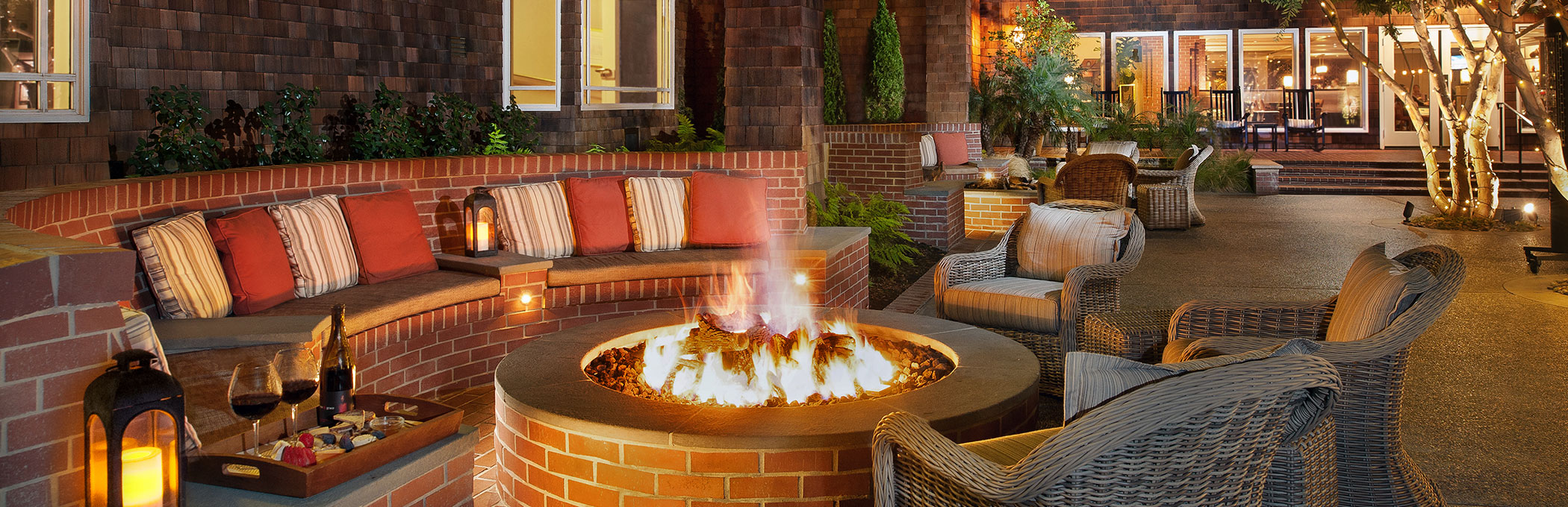 brick seating area with pillows around a fire pit