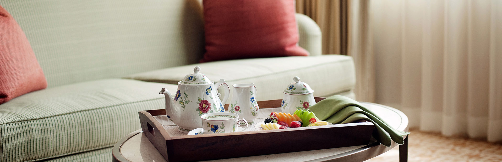 teapot and teacup on a tray on a table in front of a green couch