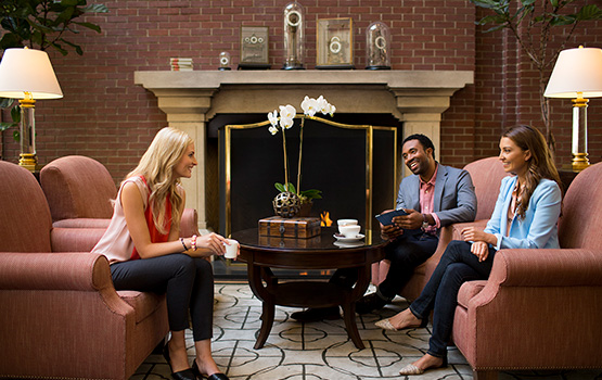 3 people sitting around a coffee table in front of a fireplace