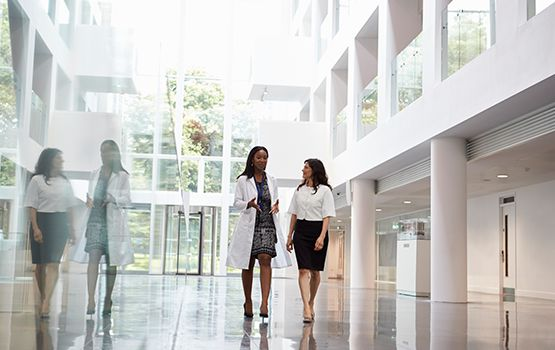two woman walking in a bright building with large windows
