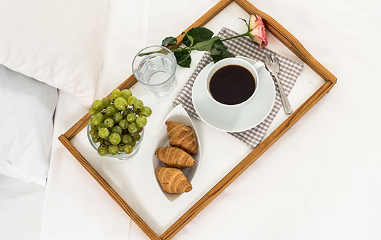 Croissants, grapes and coffee on a tray sitting on a bed