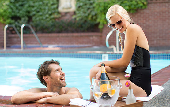 Man in pool smiling at blond woman sitting on the side of the pool