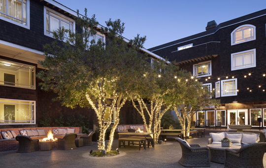 Hotel courtyard at dusk with a fire pit and seating