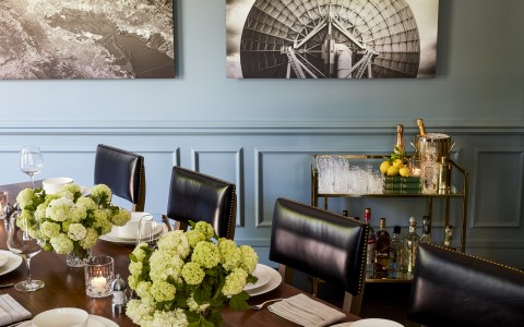 blue dining room with black leather chairs and table with flowers on it