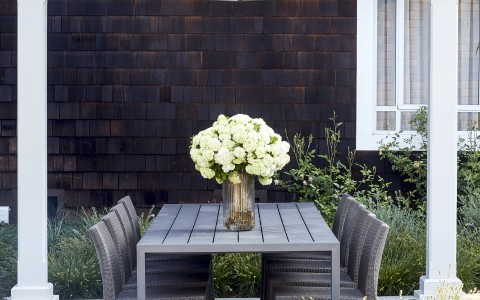 outdoor table with flowers in a vase on it