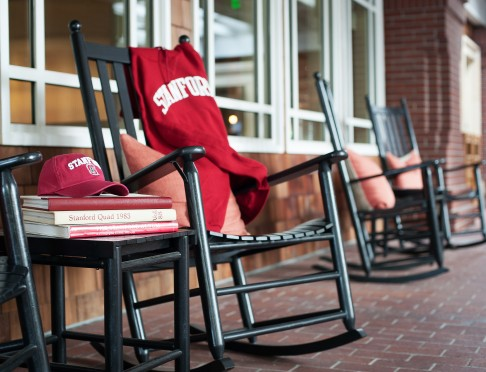 red stanford sweater on a rocking chair next to a stanford hat and books