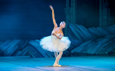 Ballerina in white tutu with bent knees and arm extended above head against blue lit stage