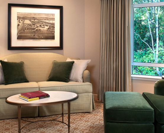 Guest room sitting area with green striped sofa and green chair by window