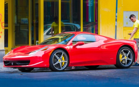 Red Ferrari in front of yellow building facade with man in yellow shirt
