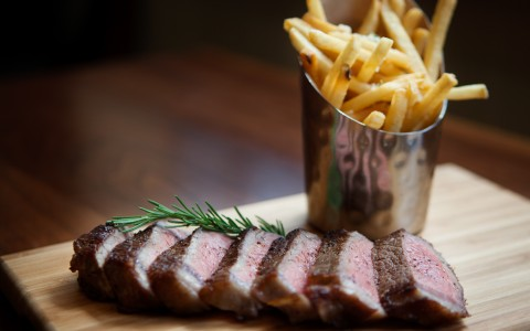 Steak cut up with french fries in a metal cup on wood surface