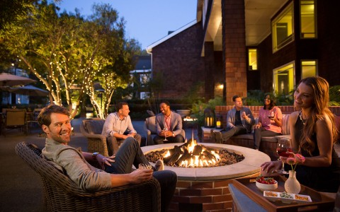 6 friends drinking wine around an outdoor firepit in the evening