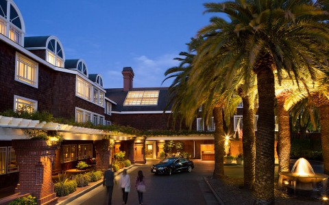 Hotel entrance at night with lighting on facade and trees