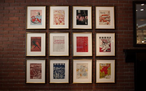 12 illustrated images in white mats and gold frames on the wall in a grid