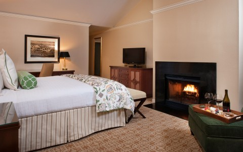 a room with a bed, table and a fireplace