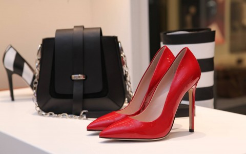 Red high heel shoes and a black hand bag