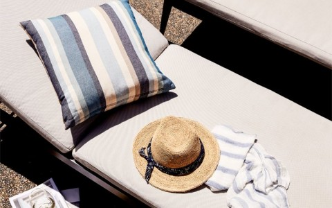 hat, towels, pillow, magazines and wine glasses by the pool