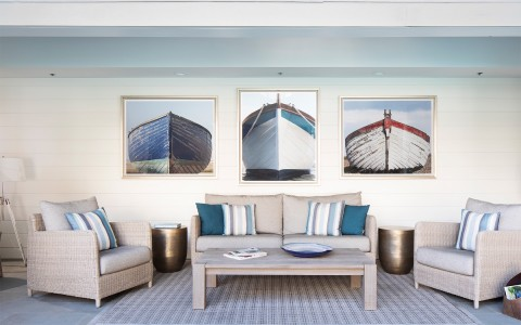 stanford park hotel gallery 1 coastal seating area with pictures of boats on the wall and a blue rug