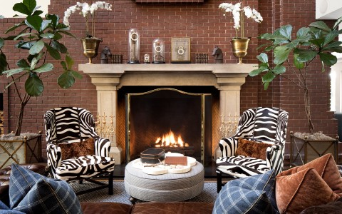 stanford park hotel gallery 9 seating area with patterned chairs and pillows next to a fire