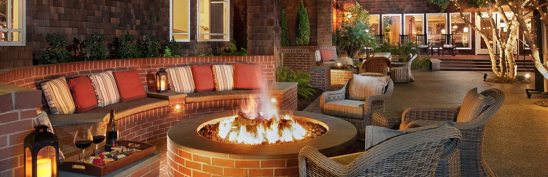 a brick seating area with chairs and pillows next to a firepit