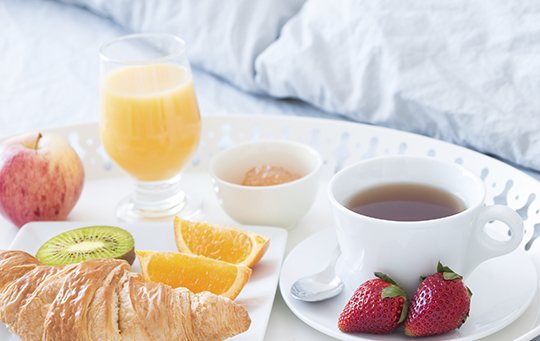 Breakfast food with orange juice and coffee on a tray