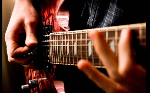 Close up on hands of guitarist while playing