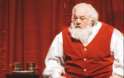 Santa in red vest and white shirt sits beside plate of milk and cookies in front of red curtain
