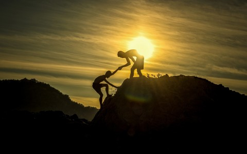 Silhouette of boy helping another climb a hill with bright sun in background