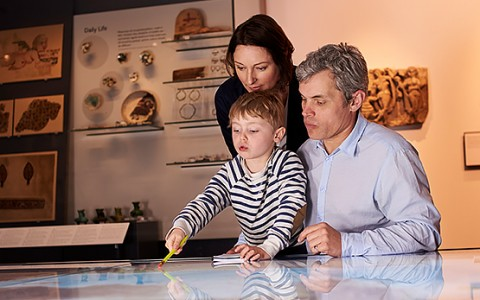 a family looking at an exhibit in the museum
