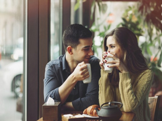 a couple enjoying cups of coffee and smiling at each other