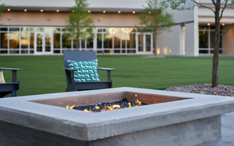 close up of a fire pit with lounge chairs around it
