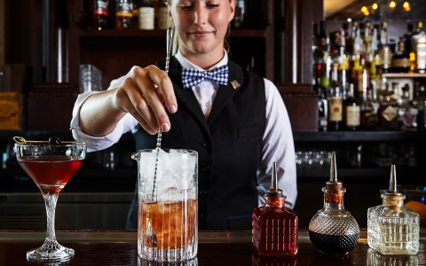 a bartender stirring a cocktail