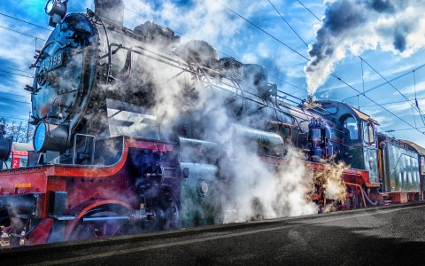 Train engine with steam rising majestically against blue sky