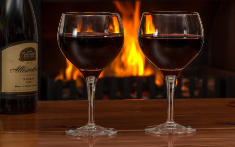 Two glasses of wine on a table with fireplace in the background
