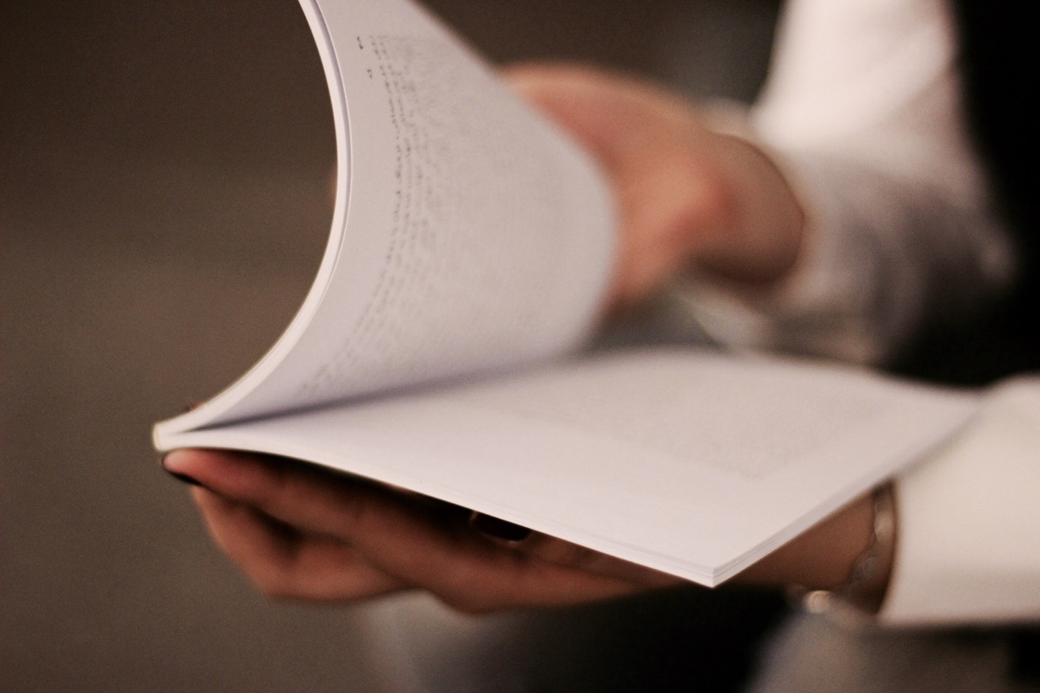 close up of hands holding paperback book