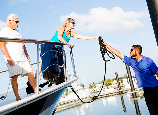 man on dock handing rope to woman on boat