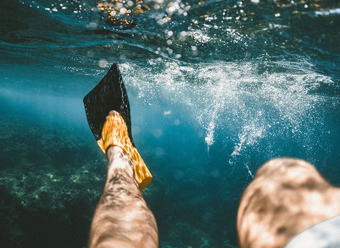 snorkling in water with yellow flippers