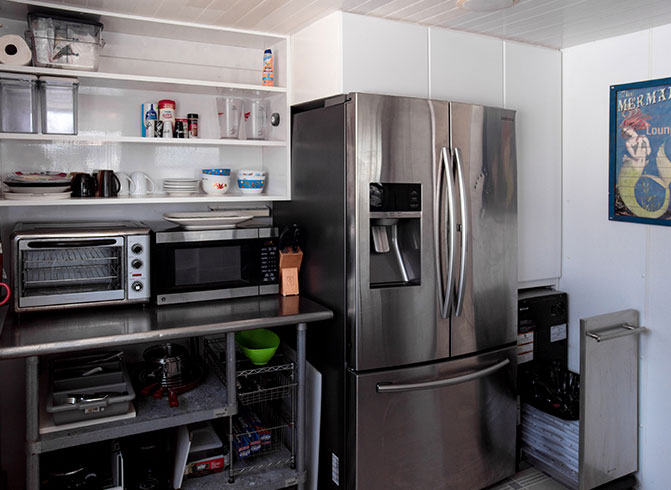 Kitchen with fridge, conventional oven, microwave & white shelving