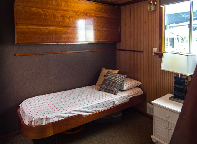 Small yacht room with twin bed & white nightstand
