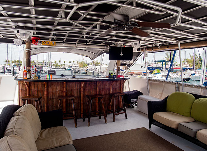 Yacht seating area with couches and tiki bar with stools