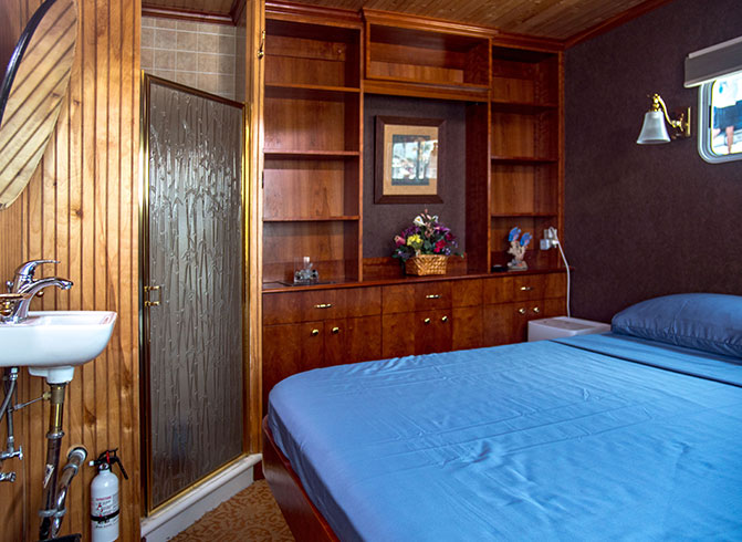 Yacht room with bed, wooden dresser & sink
