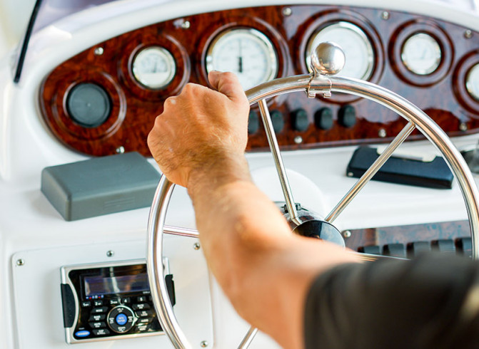 man holding a ship steering wheel