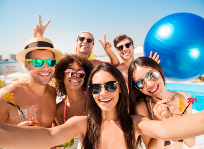group of people taking selfie at pool with beach ball